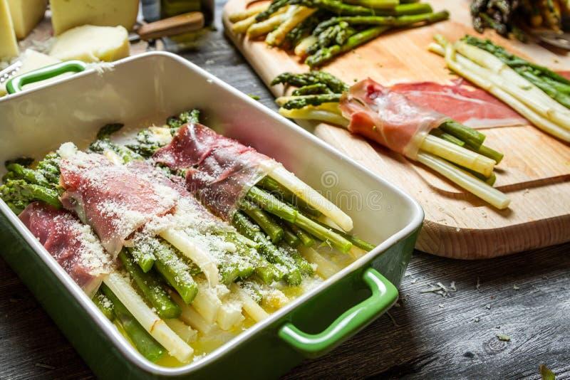 Zbliżenie staczający się w baleronie i serze asparagus zdjęcia stock