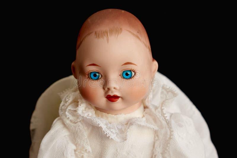Zbliżenie stara porcelany lala z niebieskimi oczami na czarnym tle zdjęcia royalty free