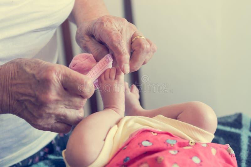 Zbliżenie starsze osoby wręcza kładzenie skarpety na nowonarodzonych ciekach zdjęcia stock
