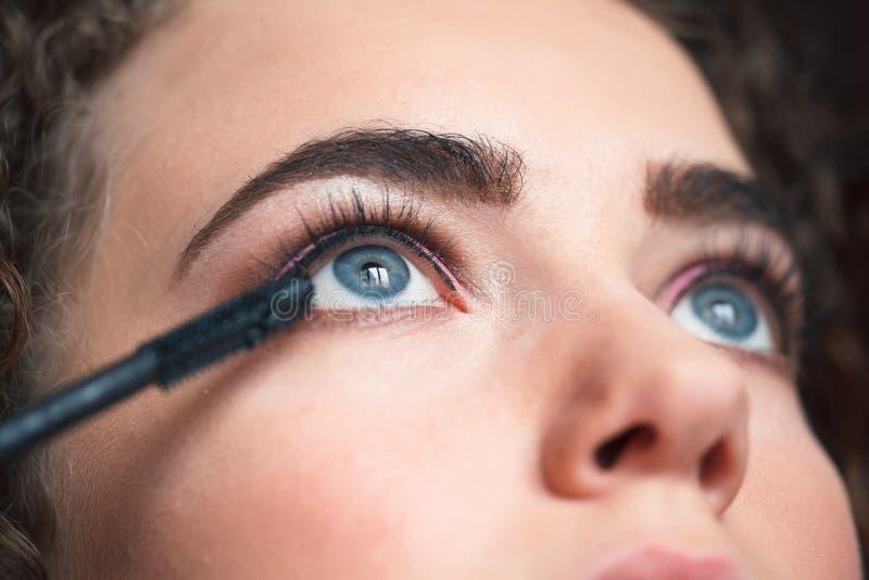 Zbliżenie stosuje smokey makeup artysta przygląda się makeup Rzęsy rozszerzenia procedura obrazy stock