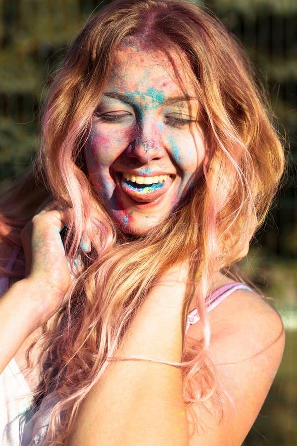 Zbliżenie strzał zakrywający z kolorowym Holi pai szczęśliwa młoda kobieta fotografia stock