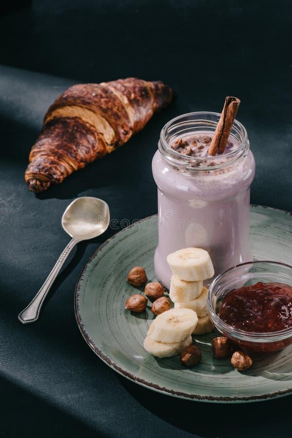 zbliżenie strzelał jagodowy smoothie z cynamonowymi słomianymi i czekoladowymi plasterkami na talerzu goleń, orzechów włoskich, d fotografia stock