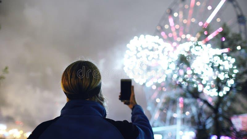 Zbliżenie sylwetka mężczyzna dopatrywanie i fotografować fajerwerki wybuchamy na smartphone kamerze outdoors fotografia royalty free