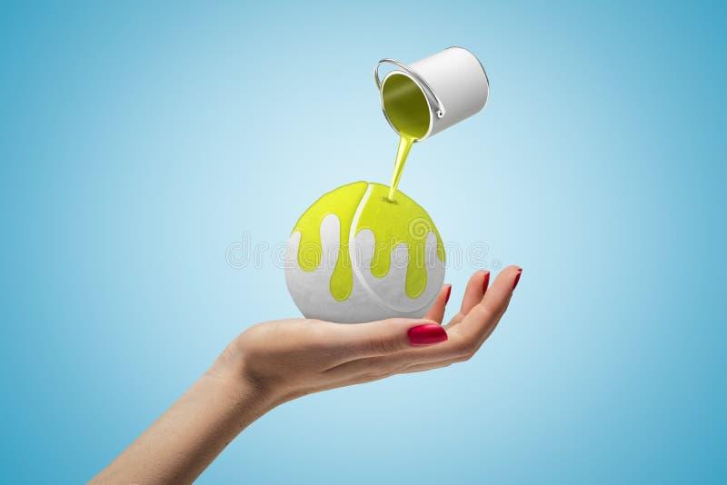 Zbliżenie trzyma białą tenisową piłkę na palmowej i małej puszce żółta farba w lotniczej dolewanie farbie na piłce kobiety ręka zdjęcie royalty free