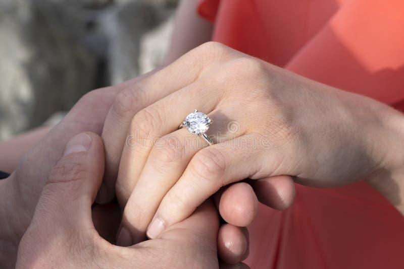 Zbliżenie trzyma kobiety rękę z diamentowym pierścionkiem mężczyzna ręka zdjęcia stock