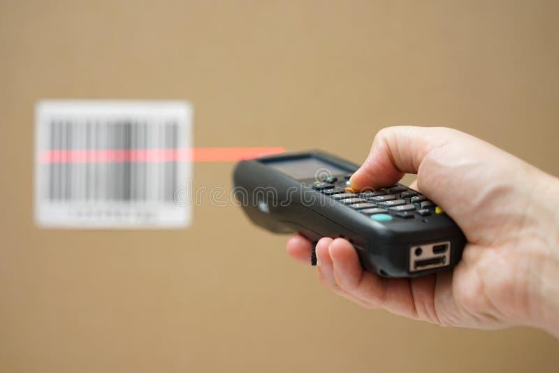 Zbliżenie trzyma prętowego kodu przeszukiwacz ręka zdjęcie stock