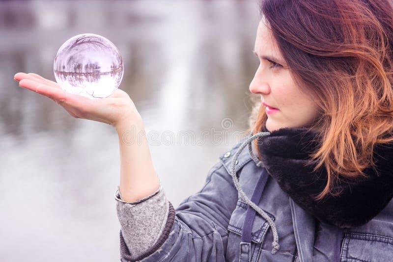 Zbliżenie trzyma szklaną sferę młoda kobieta obraz stock