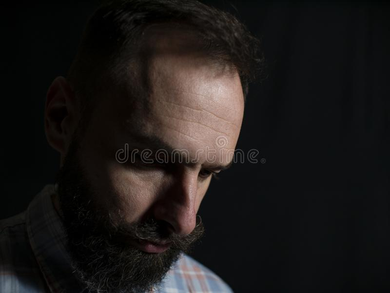 Zbliżenie twarz elegancki mężczyzna patrzeje w dół na czarnym tle z brodą i wąsy z poważną twarzą obrazy stock
