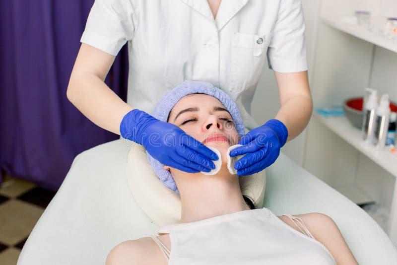 Zbliżenie twarz kobiety lying on the beach na leżance i relaksować podczas kosmetycznej procedury w kosmetologia salonie Ręki kob obrazy royalty free