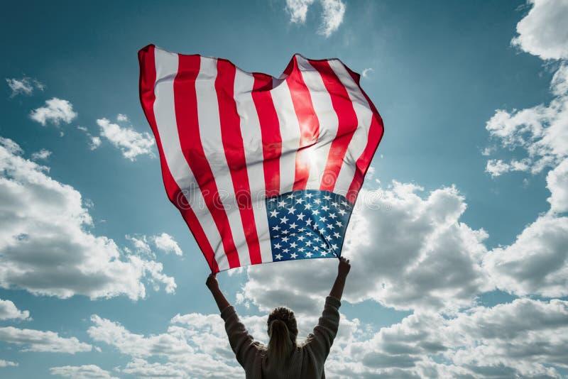 Zbliżenie tylny widok Dumna kobieta cieszy się lato zmierzch outdoors i trzyma flagę amerykańską fotografia stock