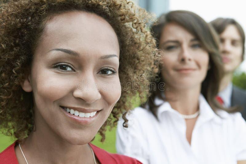 Zbliżenie Uśmiechnięta kobieta Z przyjaciółmi Behind obraz stock
