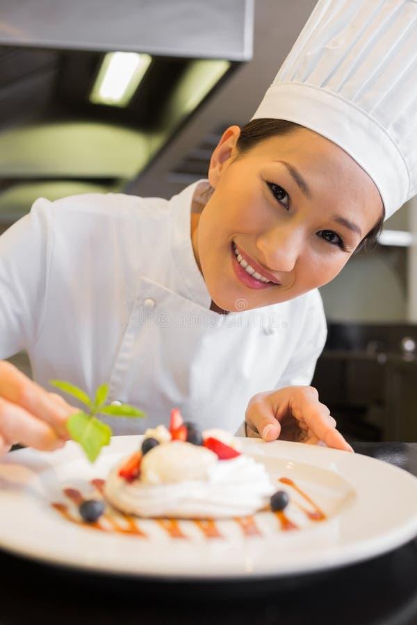 Zbliżenie uśmiechnięty szefa kuchni garnirowania jedzenie obraz royalty free