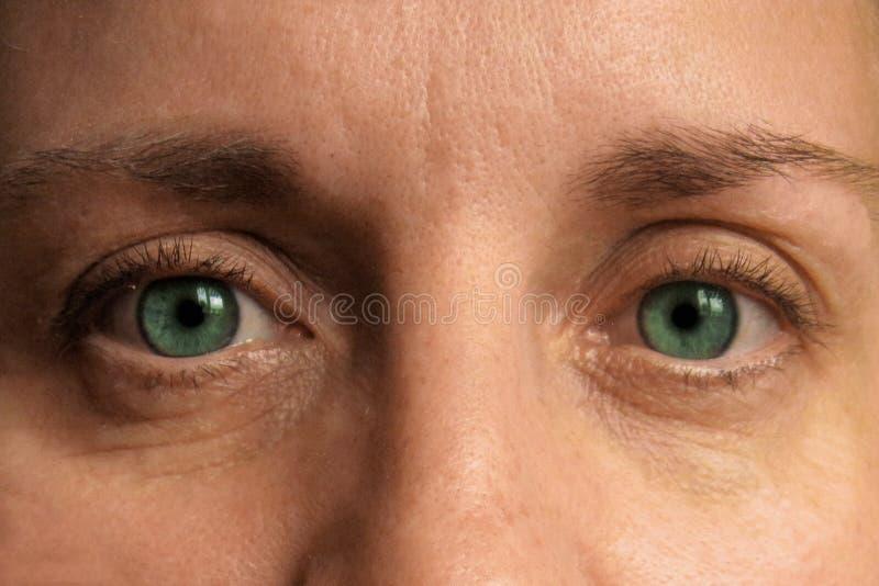 Zbliżenie w średnim wieku kobiet oczy Istna twarz uzupełnia i korekcja patrzeje kamer? zdjęcia royalty free
