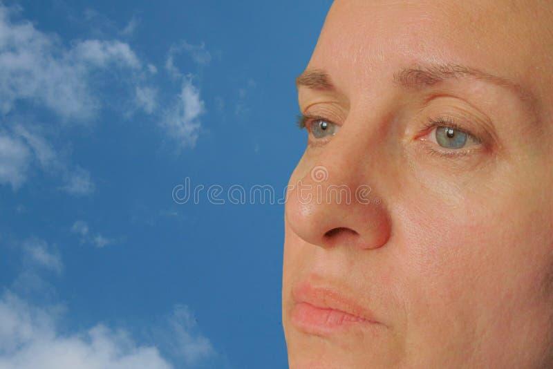 Zbliżenie w średnim wieku kobiety twarz Istna skóra uzupełnia i korekcja Don't spojrzenie przy kamerą Don't uśmiech Niebieski zdjęcie stock