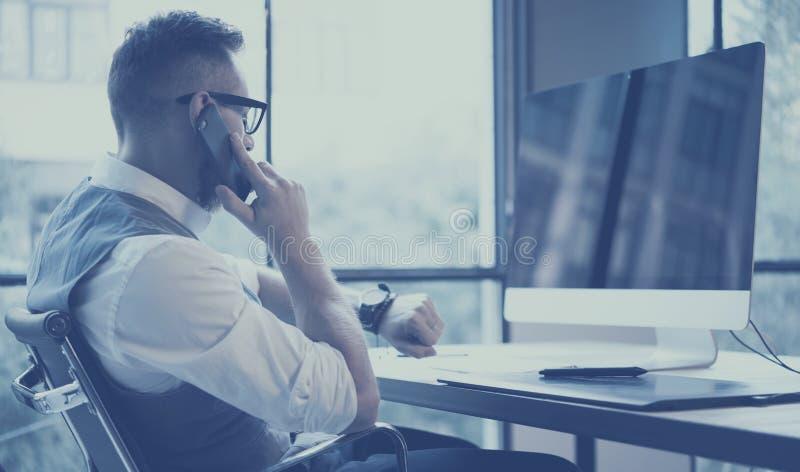 Zbliżenie widok brodaty młody biznesmen jest ubranym białą koszula i działanie, kamizelkowy przy komputerem stacjonarnym w nowoży zdjęcie stock