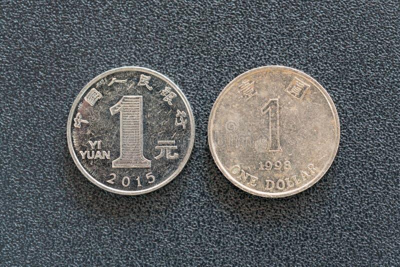 Zbliżenie widok 1 chińczyk Juan i 1 Hong kong dolarowe monety odizolowywać na ciemnym tle z kopii przestrzenią, obrazy stock