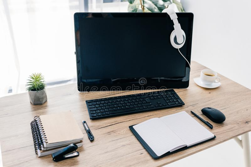 zbliżenie widok hełmofony na komputerowym monitorze, pusty podręcznik, materiały nóż, zszywacz, filiżanka zdjęcia stock