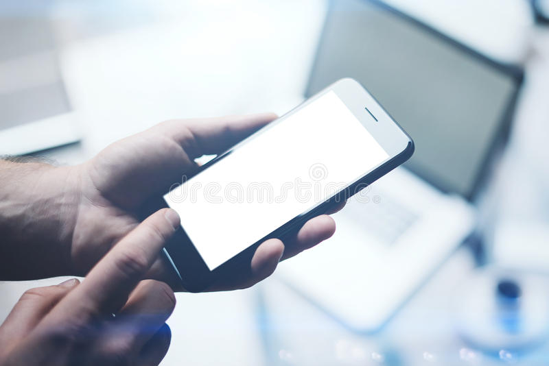 Zbliżenie widok mężczyzna ręki trzyma nowożytnego telefon komórkowego z bielu pustym ekranem i wskazuje palec stwarzać ognisko do zdjęcia royalty free