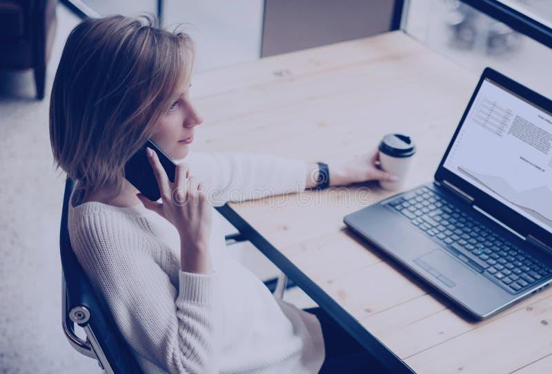 Zbliżenie widok młoda kobieta używa nowożytnego telefon komórkowego i laptop przy jej pracującym miejscem w coworking studiu podc fotografia royalty free