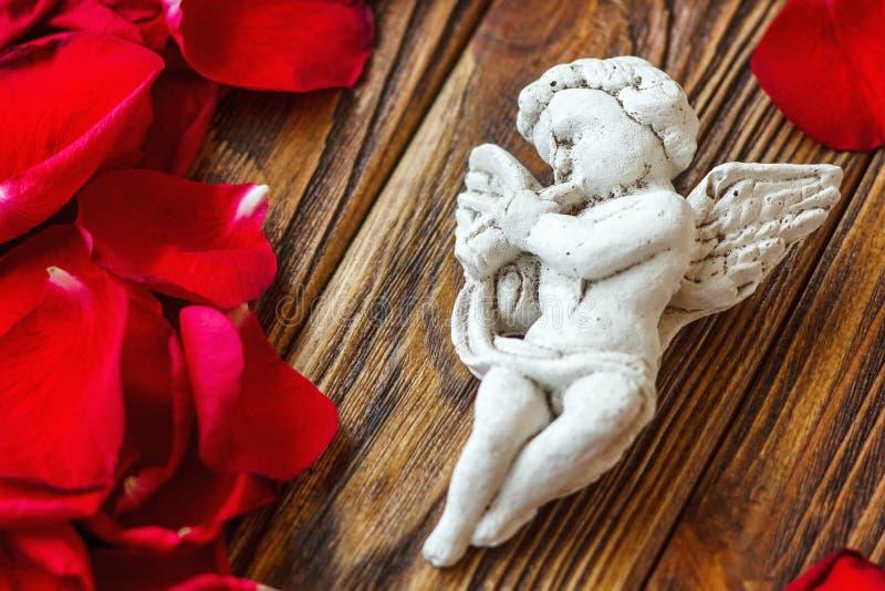 Zbliżenie widok piękny amorek z trąbką, anioł dekoracyjna figurka blisko czerwieni róży płatków na drewnianym tle zdjęcie royalty free