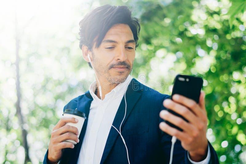 Zbliżenie widok Przystojny uśmiechnięty biznesmen używa smartphone dla listining muzyki w miasto parku podczas gdy chodzący Młody obrazy stock