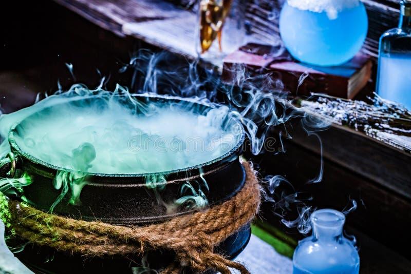Zbliżenie witcher kocioł z błękitnymi napojami miłosnymi dla Halloween obraz stock