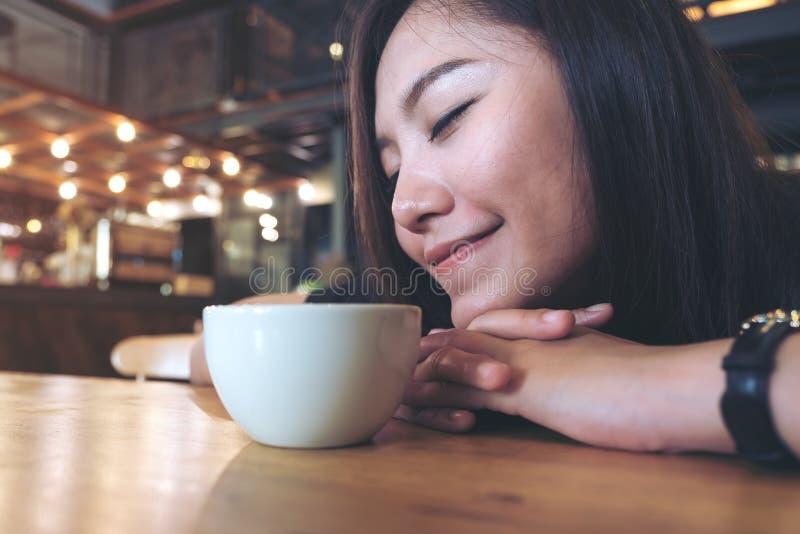 Zbliżenie wizerunek Azjatycka kobieta odpoczywa na jej przymknięciu i rękach wącha gorącą kawę na drewnianym stole z odczuciem si zdjęcia stock