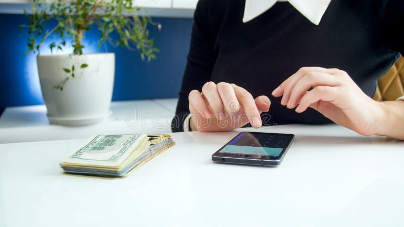 Zbliżenie wizerunek bizneswoman używa smartphone kalkulatora podczas gdy liczący pieniądze fotografia stock