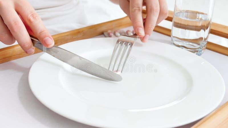 Zbliżenie wizerunek chore kobiety łasowania pigułki zamiast gościa restauracji obrazy stock