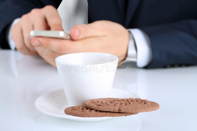 Zbliżenie wizerunek filiżanka kawy z ciastkami Biznesmena holdin zdjęcie royalty free