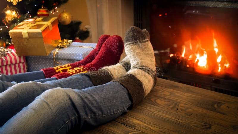 Zbliżenie wizerunek jest ubranym woolen skarpety relaksuje płonącą grabą na wigilii para zdjęcie royalty free