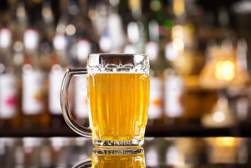 Zbliżenie wizerunek kubek z złotym zimnym lekkim piwem przy barem fotografia royalty free