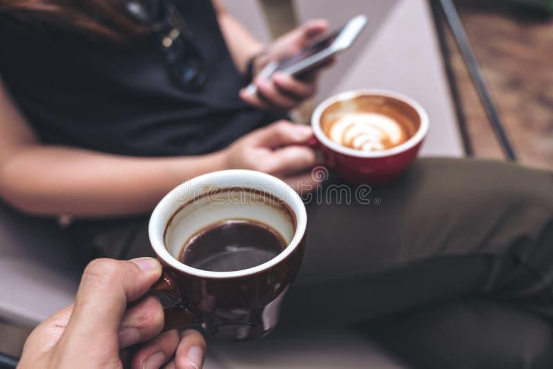 Zbliżenie wizerunek mężczyzna ` s ręka trzyma czarną filiżankę z kobietą używa smartphone podczas gdy pijący kawę zdjęcie stock