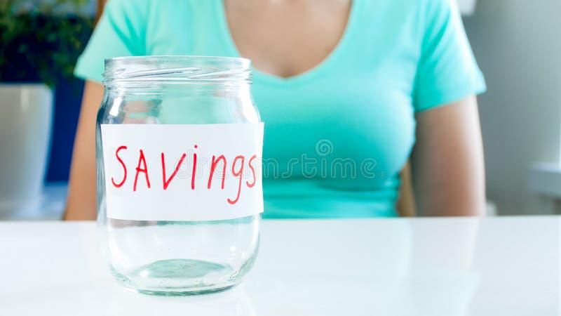 Zbliżenie wizerunek młoda kobieta siedzi z pustym szklanym słojem dla pieniędzy savings z pieniężnymi problemami zdjęcia royalty free