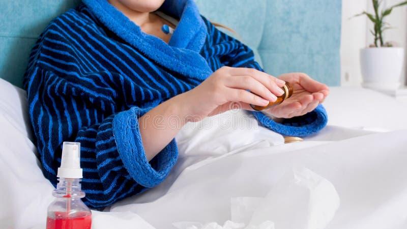 Zbliżenie wizerunek młode chore kobiety i brać medycyny out od zbiornika obrazy royalty free