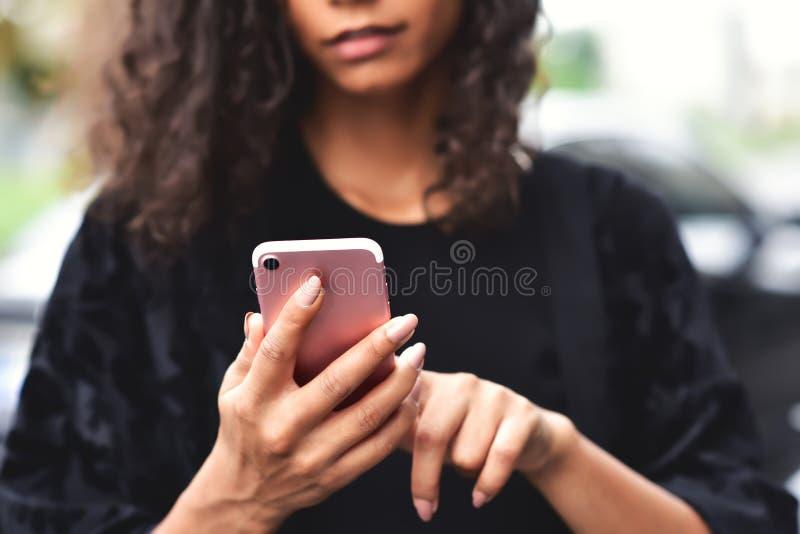 Zbliżenie wizerunek piękny mieszany biegowy kobiety mienie, używać mądrze telefon z czuć szczęśliwy i patrzejący zdjęcie stock