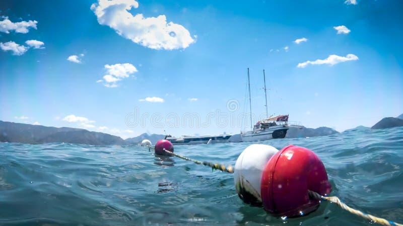 Zbliżenie wizerunek pociesza i morze macha przeciw pięknemu białemu jachtowi przy słonecznym dniem fotografia stock