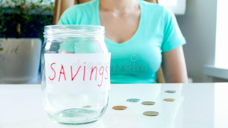 Zbliżenie wizerunek pustych pieniędzy savings szklany słój i few monety na bielu stole obrazy royalty free