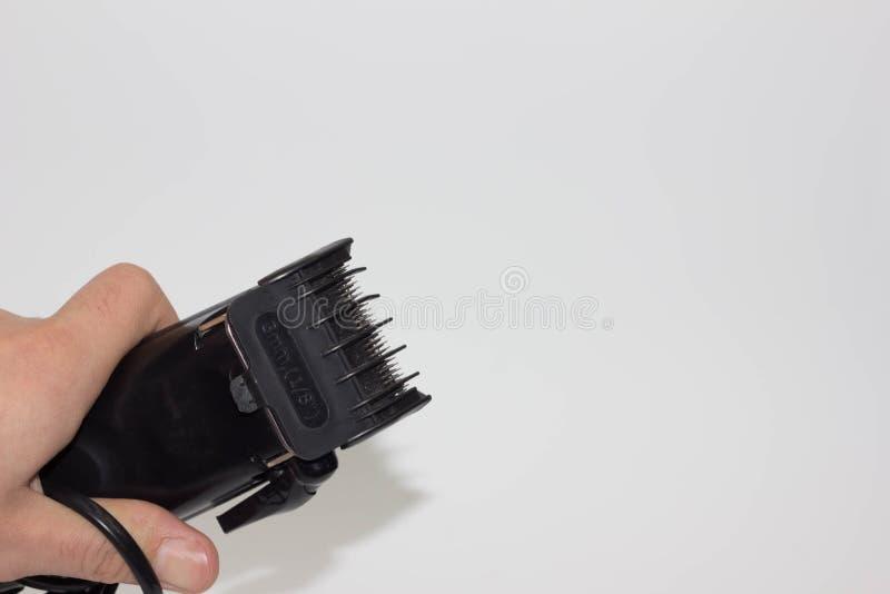 Zbliżenie wizerunek ręki mienia hairclipper, odizolowywający na białym tle, elektryczny włosiany cążki w ręce dla fryzjerów zdjęcie stock
