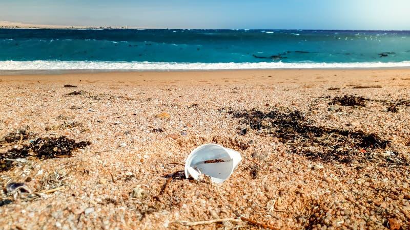 Zbliżenie wizerunek zakrywający z plastikowymi filiżankami, śmieci i gruzami morze plaża, Pojęcie ekologii katastrofa i zanieczys obrazy stock