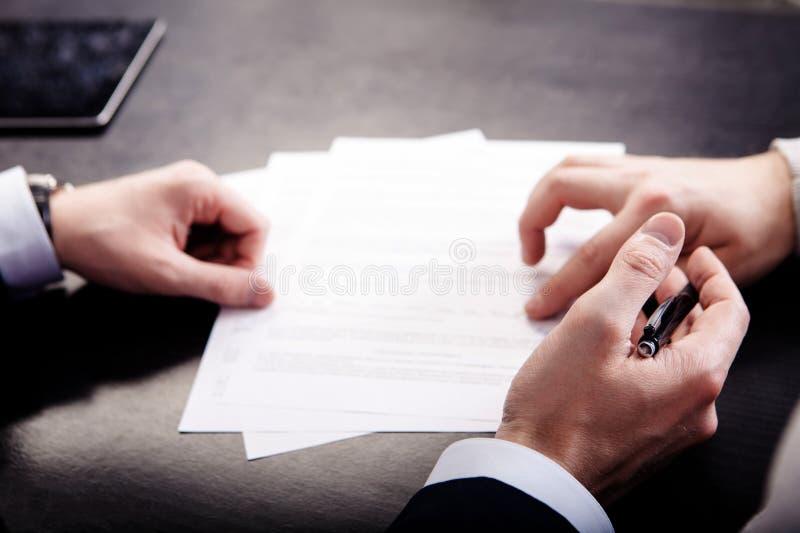 Zbliżenie wskazuje gdzie podpisywać kontrakt, legalnych papiery lub podaniową formę męska ręka, obraz royalty free