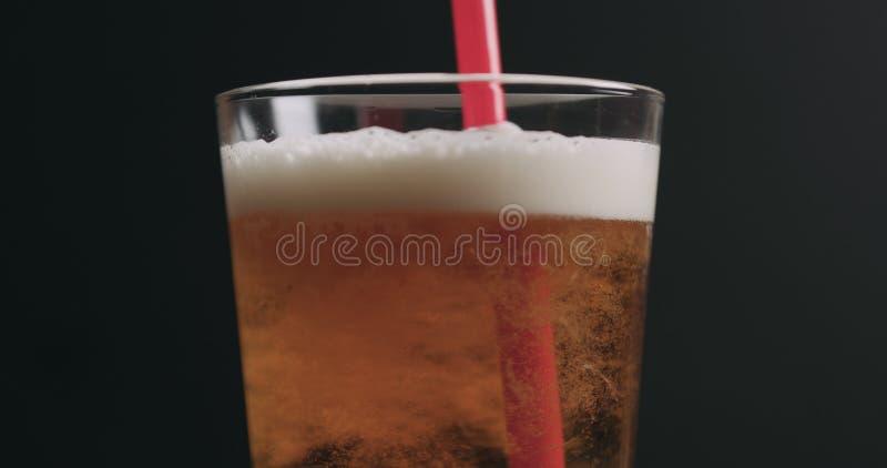 Zbliżenie zawijasa lekkiego ale piwo z bąblami nad czarnym tłem fotografia stock