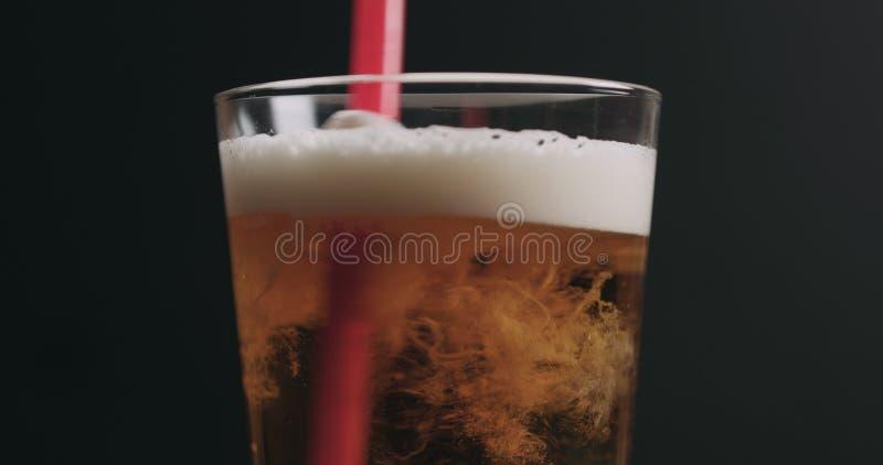 Zbliżenie zawijasa lekkiego ale piwo z bąblami nad czarnym tłem obrazy stock