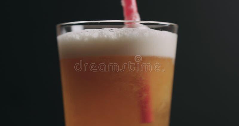 Zbliżenie zawijasa lekkiego ale piwo z bąblami nad czarnym tłem zdjęcia stock
