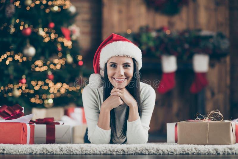 Zbliżenie zdjęcia pozytywnej radosnej dziewczyny leżącej na dywanie podłogowym z kartonowymi pudełkami na prezent podczas świątec fotografia stock