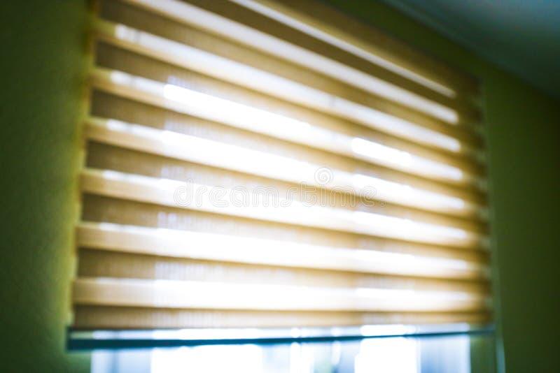 Zbli?enia br?zu koloru rolkowych stor zas?ony światło słoneczne przez rolkowej story w mieście i okno Mi?kki ostro?? wizerunek zdjęcie royalty free