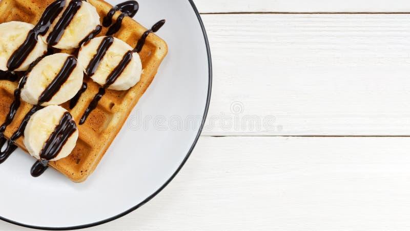 Zbli?enie domowej roboty belgijscy gofry z banan?w plasterkami nakrywaj?cymi z czekolad? na bia?ym drewnianym stole zdjęcia royalty free
