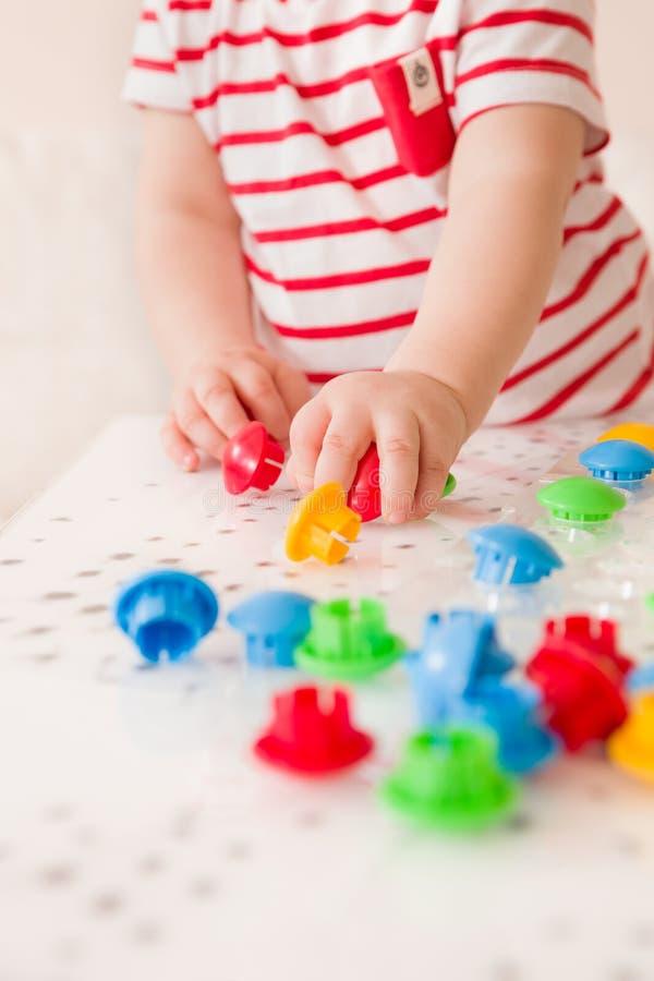 Zbli?enie dziecka ` s r?ka bierze jaskraw? mozaik? rozdziela Bawi? si? kolor w domu i ucz?cy si? Aktywno?? z dzie?mi zdjęcia stock