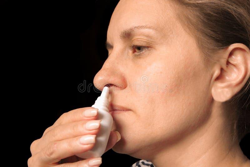Zbli?enie kapie nosowe krople w nosie w ?rednim wieku kobieta Kobiet ki?cie taktowa? zimno, gryp? lub alergi? w domu, r?k opieki  zdjęcie royalty free