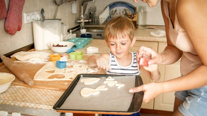 Zbli?enie portret potomstwa matkuje uczy? jej berbecia syna robi ciastkom Dziecko z matecznymi wypiekowymi deserami na pieczeniu fotografia stock